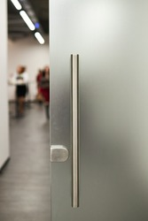 Glass frosted door with a metal handle. vertical photo
