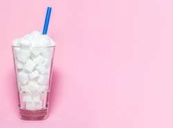 Glass full of sugar cubes - unhealthy diet concept.