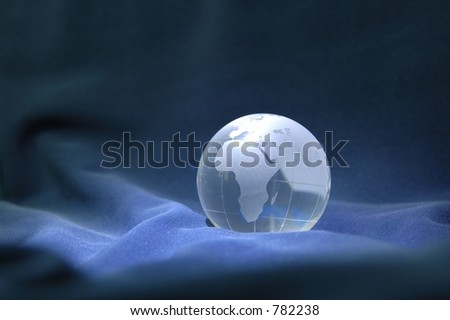 Glass globe against blue velvety background