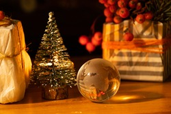 glass globe of the planet lies carriages of a small Christmas tree and boxes with gifts by candlelight in the dark, New Year's