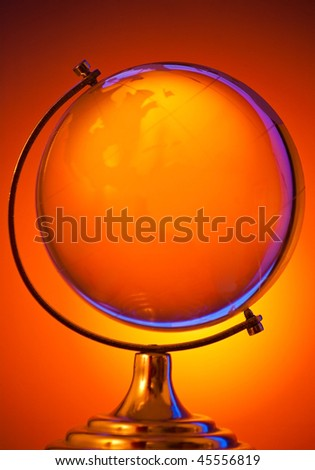 glass globe on warm background with blue reflection