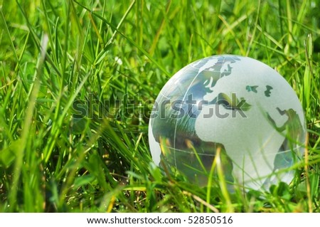 glass globe or earth in green grass showing eco concept with copyspace