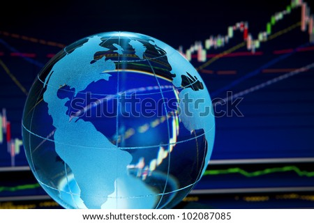 Glass globe over stock data on computer screen - stock photo
