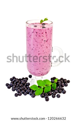 Glass goblet with a milkshake, berries and green sprig of blueberries isolated on white background