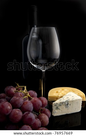Glass, grapes, bottle of wine and cheese on black background