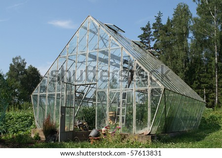 Glass greenhouse in countryside.