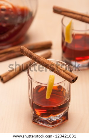glass heating red liqueur with cinnamon sticks on wood table