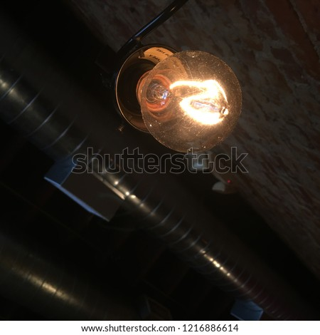 Glass incandescent light bulb with tungsten filament, looking from below with soft focus ceiling utilities behind