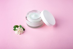 Glass jar and white cap with body cream on pink background with small white flowers. Transparent jar with face cream isolated. Cosmetic product for skin care.