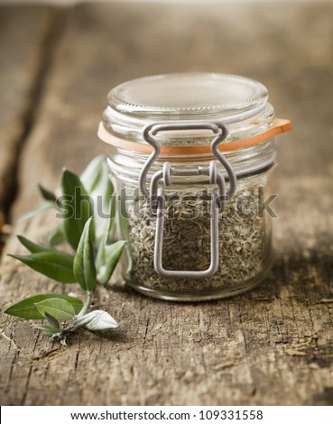 Glass jar filled with dried herbs used as an ingredient in cooking on an old rustic wooden kitchen table