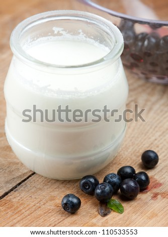 Glass jar full of creamy natural yoghurt on a wooden tabletop with fresh blueberries