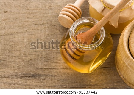 glass jar full of honey and stick on wood background