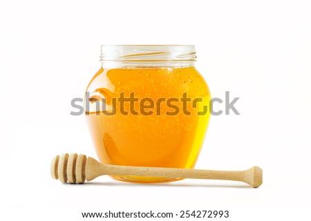 Glass jar full of honey wooden honey dipper