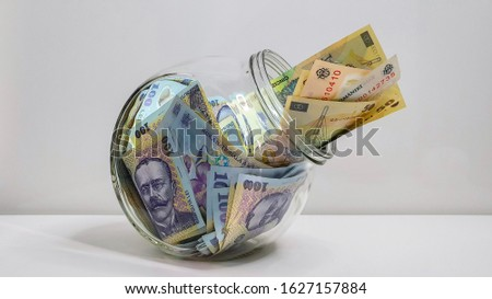 Glass Jar Full Of Romanian RON Bank Notes On A White Background Foto stock ©
