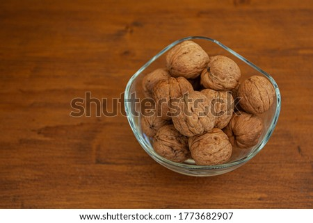 Glass jar full of walnuts with wooden background. Top view. Space for text