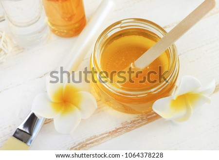 Glass jar of golden honey closep with frangipani flowers. Preparing natural beauty & body treatment at home, sweet yellow sugar nectar facial mask.