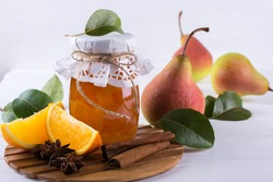 Glass jar of homemade pear and orange  jam with fresh fruits  on the white  table
