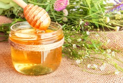 Glass jar of honey with wooden honey dipper against the background of a bouquet  of wildflowers. Close up.