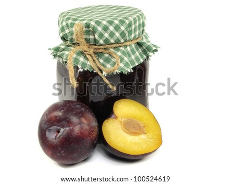 glass jar of plum jam on a white background