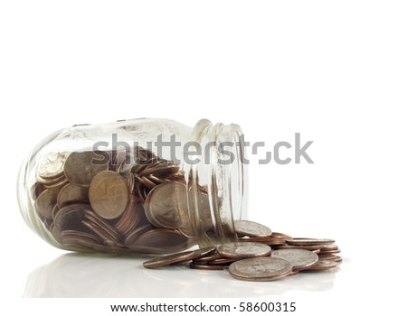 Glass jar of quarters falls over, spilling it contents