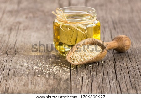 Glass jar of sesame oil and raw sesame seeds in wooden shovel with burlap sack on wooden table. Uncooked sesame background concept with copy space Foto stock ©