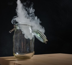 Glass jar with a lid filled with smoke on a black background. Fog in a transparent container on the table.
