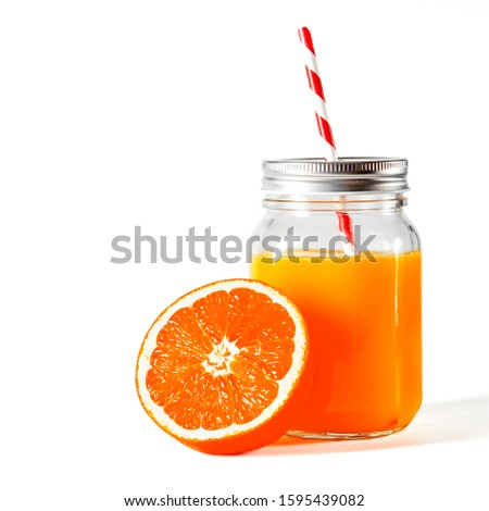 Glass jar with a tube with freshly squeezed orange juice stands on a white background next to fresh oranges
