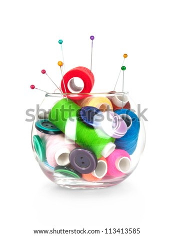 glass jar with buttons,needles, tape measuring and skeins of thread on white background