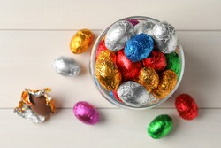 Glass jar with chocolate eggs wrapped in colorful foil on white wooden table, flat lay