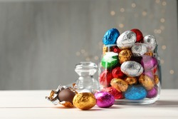 Glass jar with chocolate eggs wrapped in colorful foil on white wooden table. Space for text