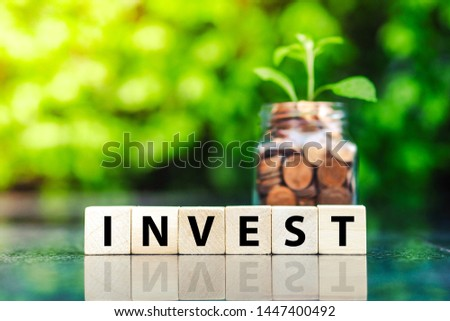 Glass jar with coins and the word invest on wood block. Financial and investment concept.