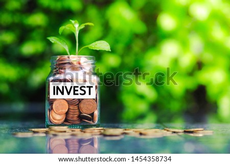 Glass jar with coins and the word invest paper label. Financial and investment concept.