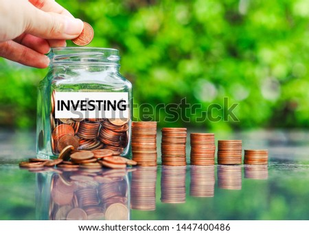 Glass jar with coins and the word investing paper label. Financial and investment concept.