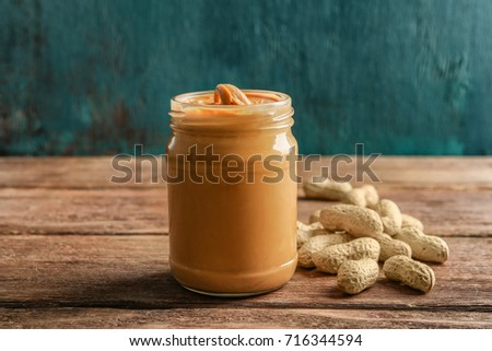 Glass jar with creamy peanut butter on wooden table #716344594