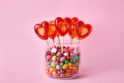 Glass jar with different candies on pink background