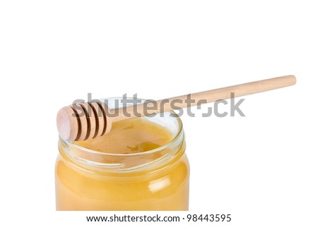 Glass jar with honey and wooden stick isolated on white background.