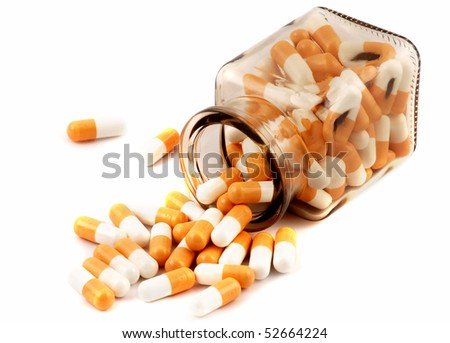 Glass jar with medical pills inside and outside isolated on white