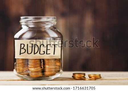 Glass jar with money and a sticker with the words BUDGET, on a wooden table.