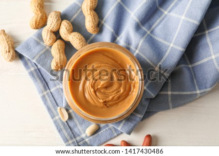 Glass jar with peanut butter, peanut and kitchen towel on white wooden background, space for text and top viewGlass jar with peanut butter, peanut and kitchen towel on white wooden background
