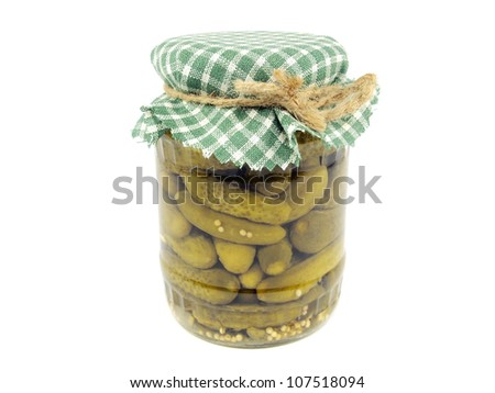Glass jar with pickled cucumbers on a white background