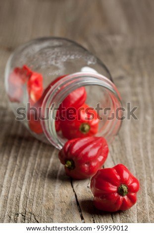 Glass jar with red chili habanero peppers on old wooden table