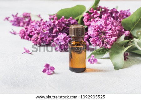 Glass jar with rose water and lilac flowers, copy space for text. Close up. Concept for spa and aromatherapy.