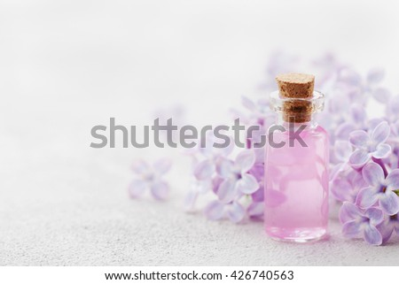 Glass jar with rose water and lilac flowers for spa and aromatherapy, copy space for text