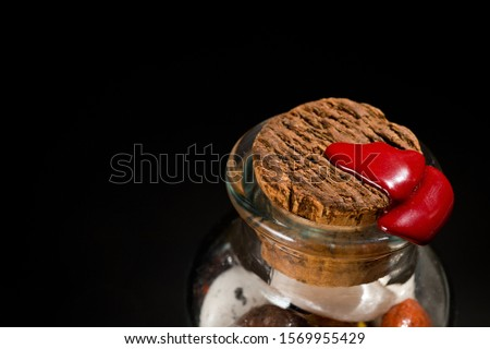 Glass jar with sweets closed by a cork and sealed with sealing wax shot on a dark background.