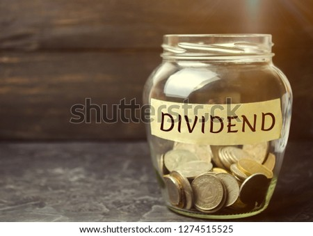 Glass jar with the word Dividend. A dividend is a payment made by a corporation to its shareholders as a distribution of profits. Concept business finance and investment. Saving money. Dividend tax