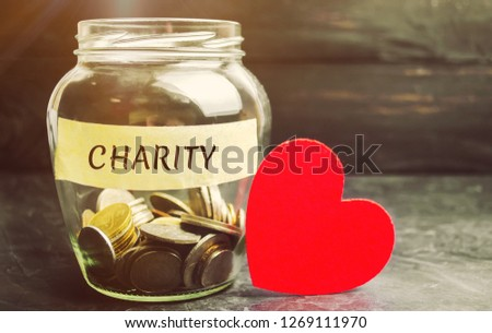 Glass jar with the words Charity and the heart. The concept of accumulating money for donations. Saving. Social medical help from volunteers. Charitable foundation