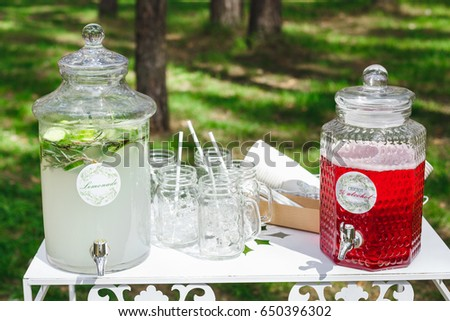 Glass jars of fresh lemonade on wedding candy bar. Summer party and reception in forest