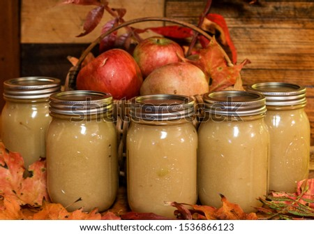 Glass Jars of homemade applesauce on a wooden board with autumn leaves and a basket of fresh apples stock photo