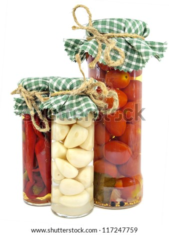 Glass jars of preserved tomatoes, garlic and red hot peppers on a white background