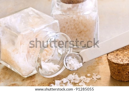 Glass jars of sea salt with a spoon on a white textured surface. Close up details.